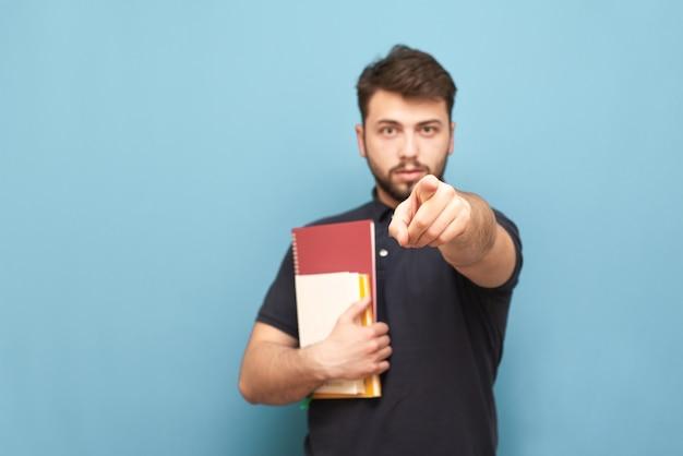 Mannelijke student met boeken in zijn handen staat op blauw en toont de wijsvinger die een zwart shirt draagt