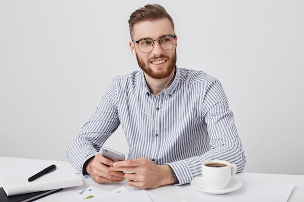 Mannelijke student met modieus kapsel, draagt een gestreept overhemd, drinkt koffie en luistert naar favoriete muziek