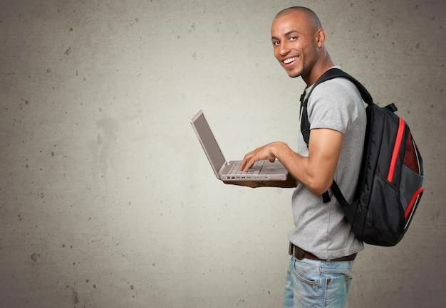 Mannelijke student met rugzak op achtergrond