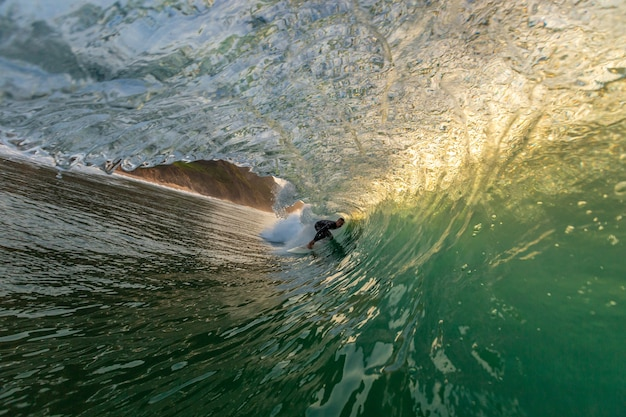 Mannelijke surfer doet trucjes die de sterke golven van de oceaan in de algarve, portugal overnemen