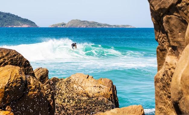 Mannelijke surfer in een golvende zee