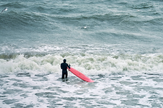 Mannelijke surfer in zwart zwempak in oceaan met rode surfplank die op grote golf wacht. warme dag, prachtig zeewater, natuurtafereel. sport en outdoor activiteit concept.