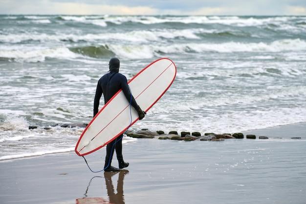 Mannelijke surfer in zwarte zwembroek die langs zee loopt en witte surfplank in zijn hand houdt. warme dag, mooie bewolkte hemel, natuurscène. sport en outdoor activiteiten concept.