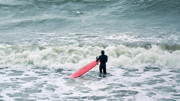 Mannelijke surfer in zwarte zwembroek in oceaan met rode surfplank wachten op grote golf. warme dag, prachtig zeewater, natuurscène