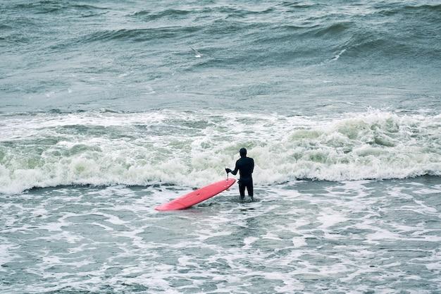 Mannelijke surfer in zwarte zwembroek in zee met rode surfplank wachten op grote golf. warme bewolkte dag, golvend oceaanwater, natuurscène. outdoor activiteit concept.