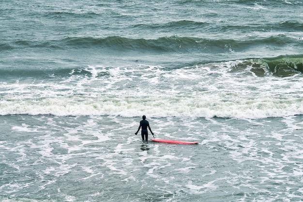 Mannelijke surfer in zwarte zwembroek in zee met rode surfplank wachten op grote golf. warme bewolkte dag, golvend oceaanwater, natuurscène