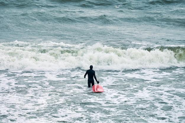 Mannelijke surfer in zwarte zwembroek in zee met rode surfplank wachten op grote golf.