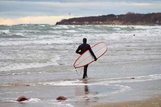 Mannelijke surfer in zwarte zwembroek wandelen langs zee en witte surfplank in zijn hand te houden Premium Foto
