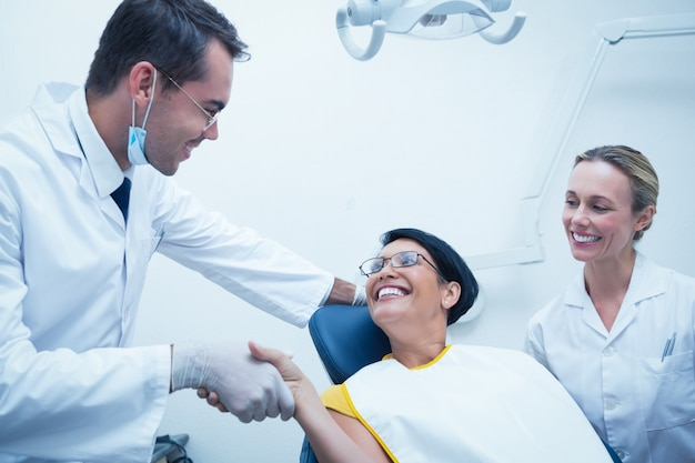 Mannelijke tandarts die handen met vrouw schudden