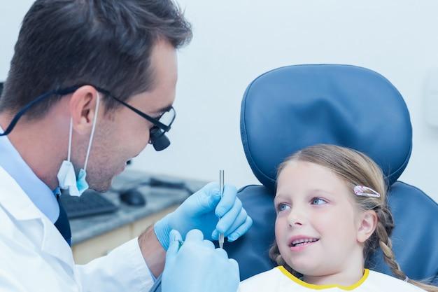Mannelijke tandarts die meisjestanden onderzoekt