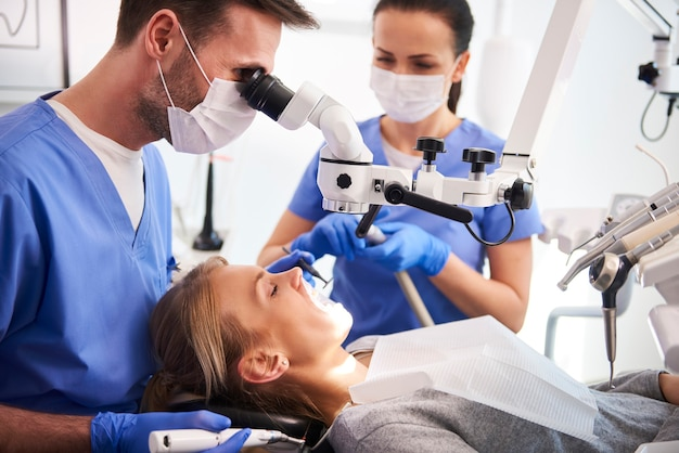 Mannelijke tandarts die met tandmicroscoop werkt