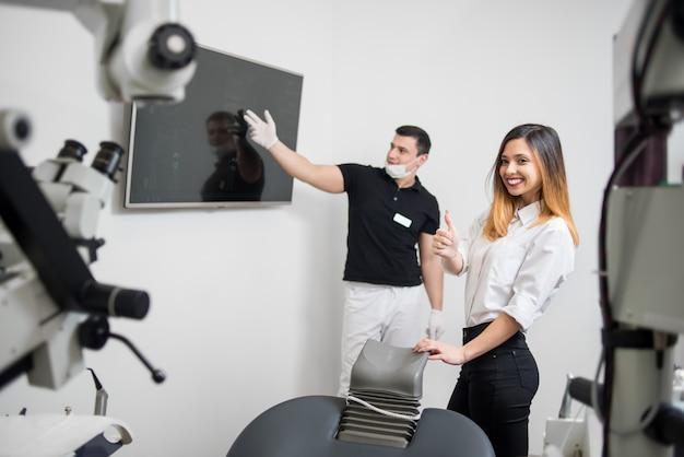 Mannelijke tandarts die tand x-ray beeld op computermonitor tonen in een tandkliniek. tandheelkunde