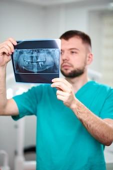 Mannelijke tandarts die x-ray houdt