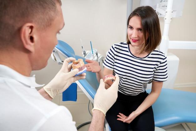 Mannelijke tandarts die zijn vrouwelijke patiënt tandimplantaat toont