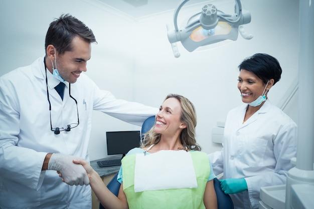 Mannelijke tandarts met assistent schudden handen met vrouw Premium Foto