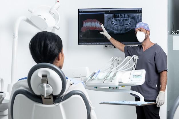 Mannelijke tandarts wijzend op een röntgenfoto voor een vrouwelijke patet zittend op een stoel in een kliniekkamer
