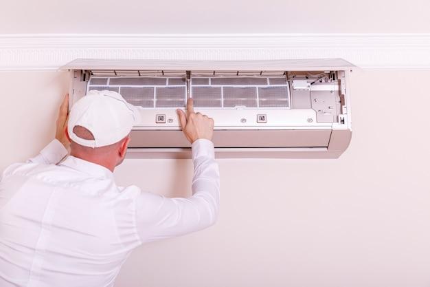 Mannelijke technicus die airconditioner binnen herstelt. jonge mens die airconditioner op de muur herstelt.