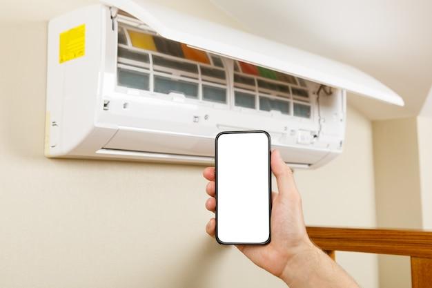 Mannelijke technicus die airconditioner binnenshuis schoonmaakt. slimme diagnose via telefoon