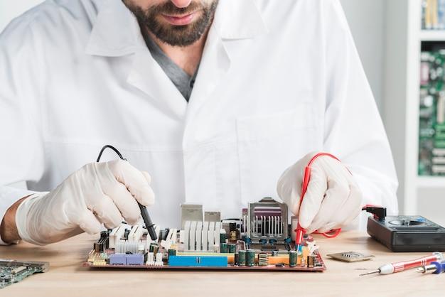 Mannelijke technicus die computer met digitale multimeter op houten bureau controleert