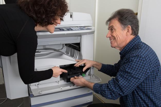 Mannelijke technicus die een printer of een kopieermachine op het werk herstelt