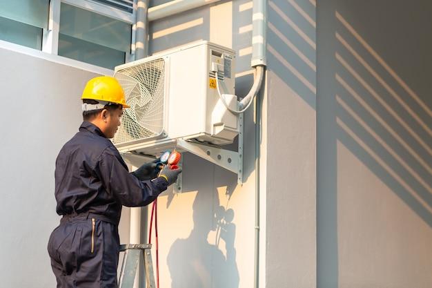 Mannelijke technicus die uniforme de veiligheid van de airconditioner herstelt