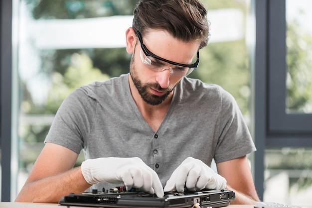 Mannelijke technicus in veiligheidsbril die computer herstelt