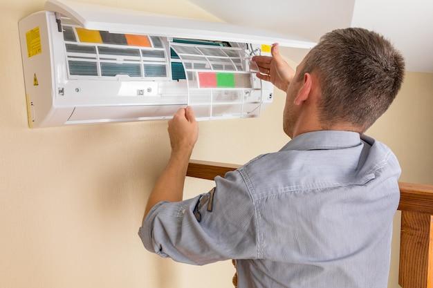 Mannelijke technicus schoonmakende airconditioner binnen