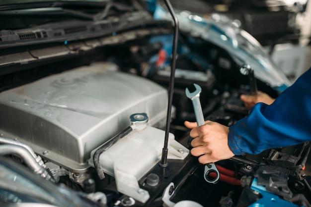 Mannelijke technicus werkt met automotor