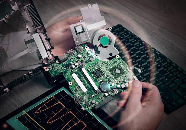 Mannelijke technologie repareert moederbord van laptop