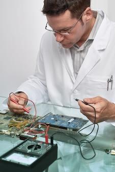 Mannelijke technologie van senor bevestigt moederbord in computerreparatiewerkplaats. getinte afbeelding, ondiepe dof