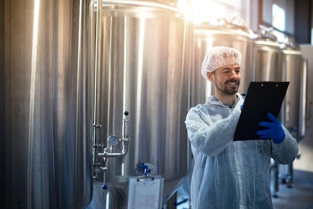 Mannelijke technoloog in wit beschermend pak die de productie in de voedsel- of drankenfabriek controleert.