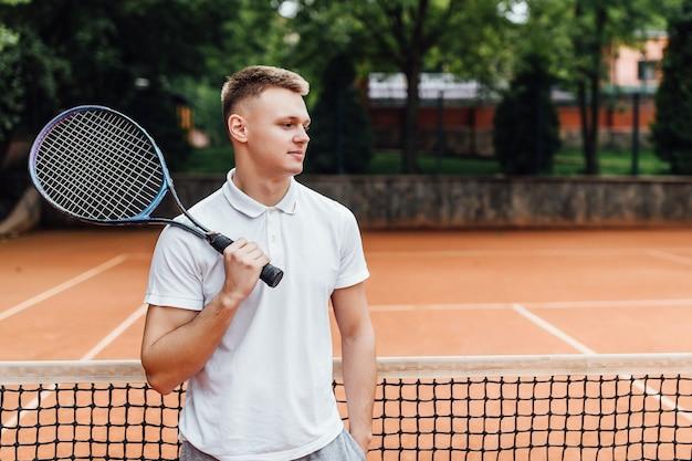 Mannelijke tennisser aan het hof die er gelukkig uitziet terwijl hij een racket vasthoudt.
