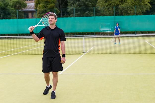 Mannelijke tennisser die een sportkleding draagt en een racket op zijn schouder houdt na een wedstrijd die zich op de tennisbaan bevindt