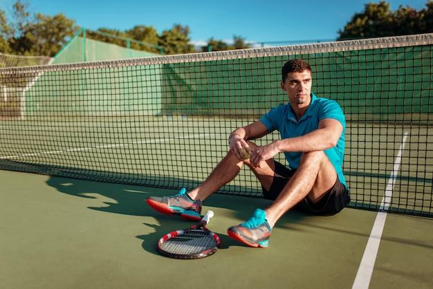 Mannelijke tennisser zittend op de grond na de training, buitenbaan.