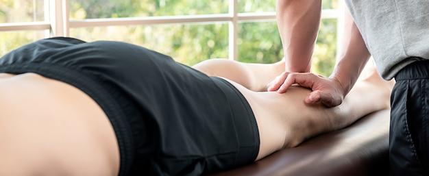 Mannelijke therapeut die beenmassage geeft aan atleetpatiënt in kliniek