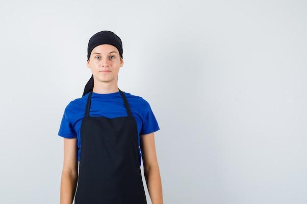 Mannelijke tiener kok in t-shirt, schort poseren terwijl hij staat en er zelfverzekerd uitziet, vooraanzicht.