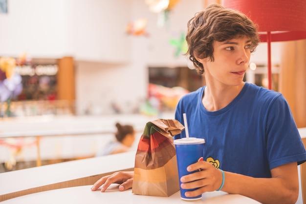 Mannelijke tiener met een fastfoodpakket aan tafel wachtend op een bestelling an