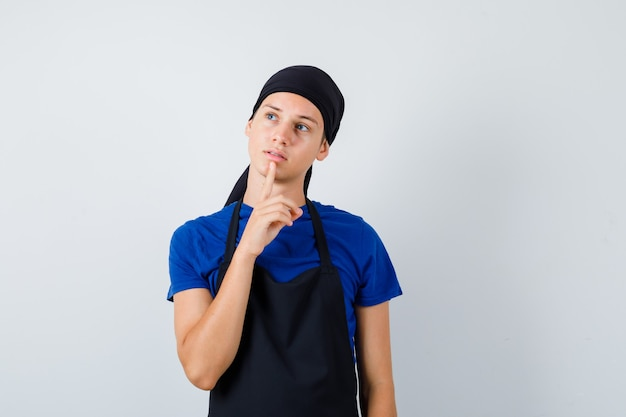 Mannelijke tienerkok die de vinger op de kin houdt in t-shirt, schort en er gepreoccupeerd uitziet. vooraanzicht.