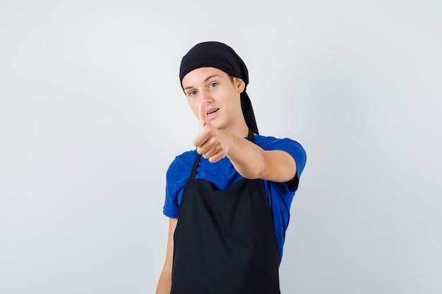 Mannelijke tienerkok die duim toont in t-shirt, schort en tevreden kijkt, vooraanzicht.