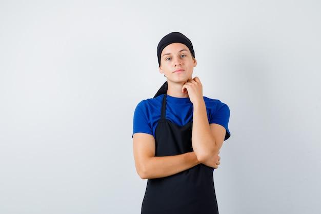 Mannelijke tienerkok houdt hand op nek in t-shirt, schort en ziet er zelfverzekerd uit. vooraanzicht.