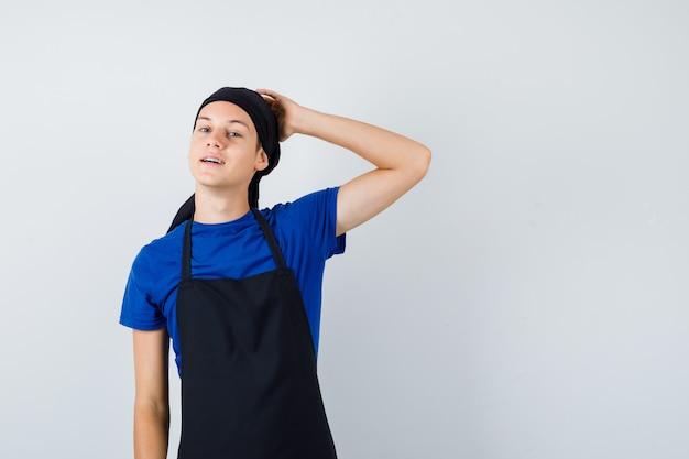 Mannelijke tienerkok in t-shirt, schort die de hand op het hoofd houdt en er charmant uitziet, vooraanzicht.