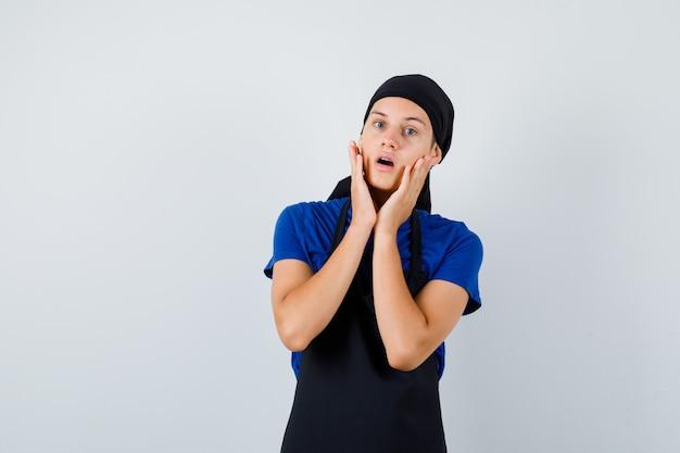 Mannelijke tienerkok in t-shirt, schort die de handen op de wangen houdt, de mond opent en er geschokt uitziet, vooraanzicht.