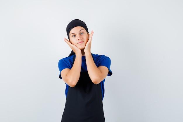 Mannelijke tienerkok in t-shirt, schort die de handen op de wangen houdt en er zelfverzekerd uitziet, vooraanzicht.