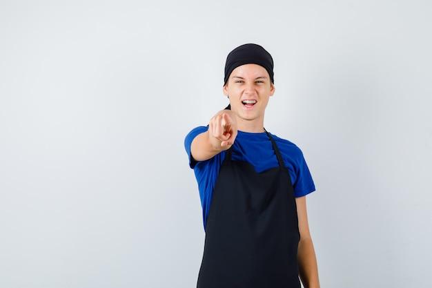 Mannelijke tienerkok in t-shirt, schort naar voren wijzend en vrolijk, vooraanzicht.