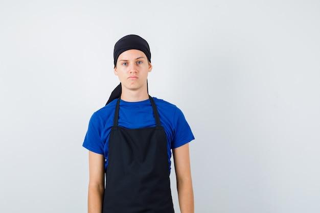 Mannelijke tienerkok poseren in t-shirt en schort en ziet er zelfverzekerd uit, vooraanzicht.