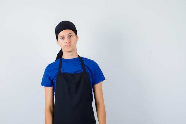 Mannelijke tienerkok poseren terwijl hij in een t-shirt, schort staat en er ontevreden uitziet. vooraanzicht.
