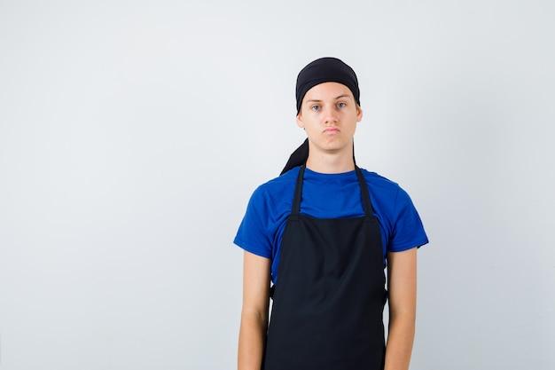 Mannelijke tienerkok poseren terwijl hij in t-shirt, schort staat en er serieus uitziet, vooraanzicht.