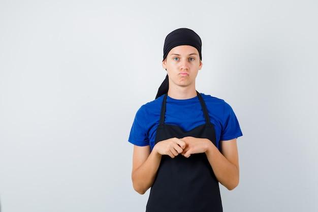 Mannelijke tienerkok staat in denkende pose in t-shirt, schort en ziet er attent uit. vooraanzicht.