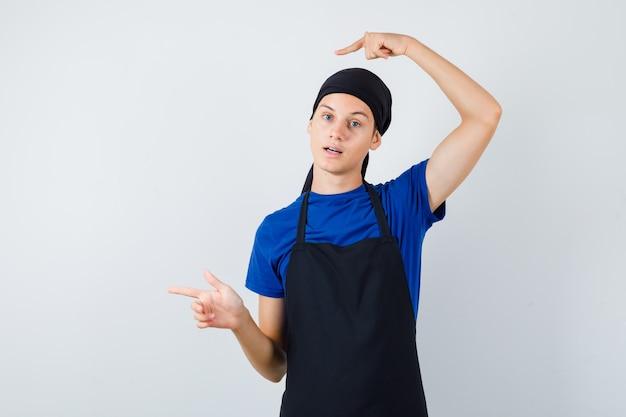 Mannelijke tienerkok wijst naar de linkerkant in t-shirt, schort en kijkt verrast, vooraanzicht.