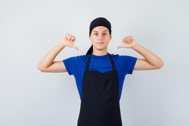 Mannelijke tienerkok wijst naar zichzelf met duimen in t-shirt, schort en ziet er zelfverzekerd uit. vooraanzicht.